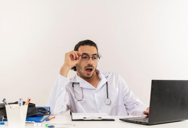 Zaskoczony, młody lekarz mężczyzna z okularami medycznymi na sobie szlafrok medyczny ze stetoskopem