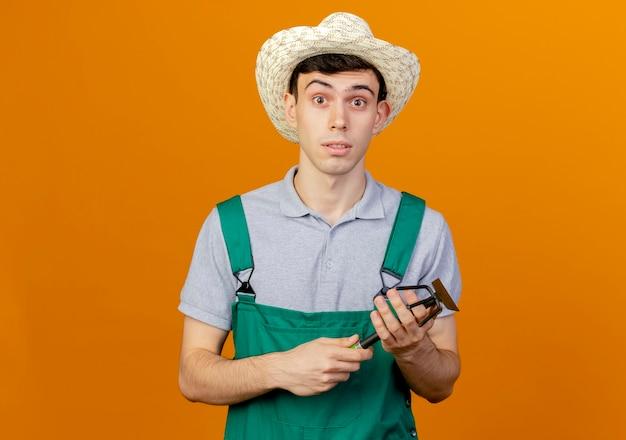 Zaskoczony młody męski ogrodnik w kapeluszu ogrodnictwo trzyma motyka grabie