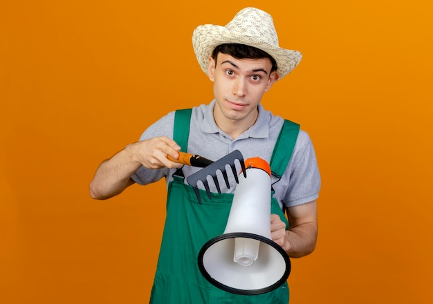 Zaskoczony młody męski ogrodnik w kapeluszu ogrodniczym trzyma głośnik i grabie
