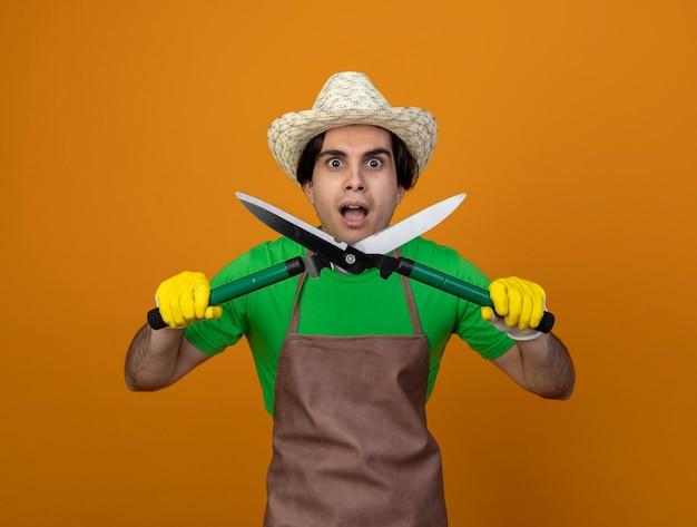 Zaskoczony młody męski ogrodnik w mundurze na sobie kapelusz ogrodniczy z rękawiczkami, trzymając maszynkę do strzyżenia