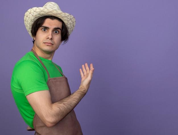 Zaskoczony, młody mężczyzna ogrodnik w mundurze nosząc ogrodniczy kapelusz wskazuje ręką z tyłu