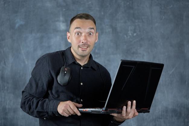 Zaskoczony młody mężczyzna patrzy w kamerę z laptopem w rękach