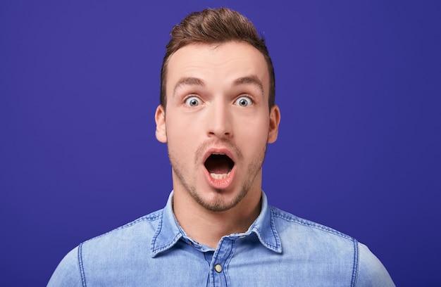 Zaskoczony młody mężczyzna w niebieskiej dżinsowej koszuli stojący z dwoma stojącymi z otwartymi ustami