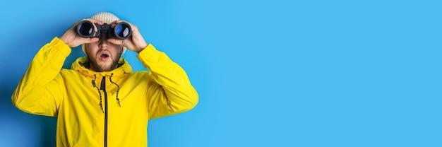 Zaskoczony młody mężczyzna w żółtej kurtce patrzy przez lornetkę w bok