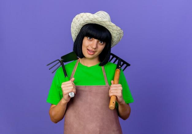 Zaskoczony młody ogrodnik kobiece w mundurze na sobie kapelusz ogrodniczy posiada grabie i motyka