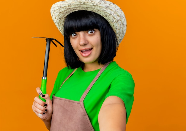 Zaskoczony młody ogrodnik kobiece w mundurze na sobie kapelusz ogrodniczy posiada grabie motyka