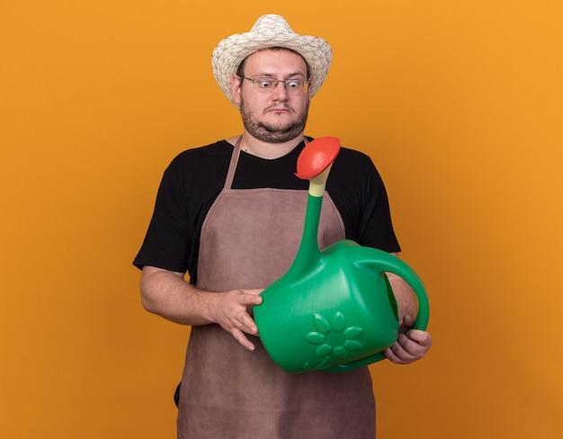 Zaskoczony młody ogrodnik mężczyzna ubrany w kapelusz ogrodniczy trzymając i patrząc na konewkę na białym tle na pomarańczowej ścianie