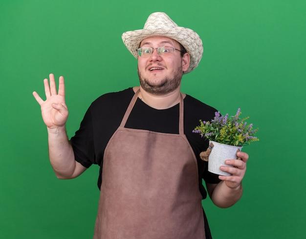 Zaskoczony młody ogrodnik mężczyzna w kapeluszu ogrodnictwo trzyma kwiat w doniczce pokazując cztery na białym tle na zielonej ścianie