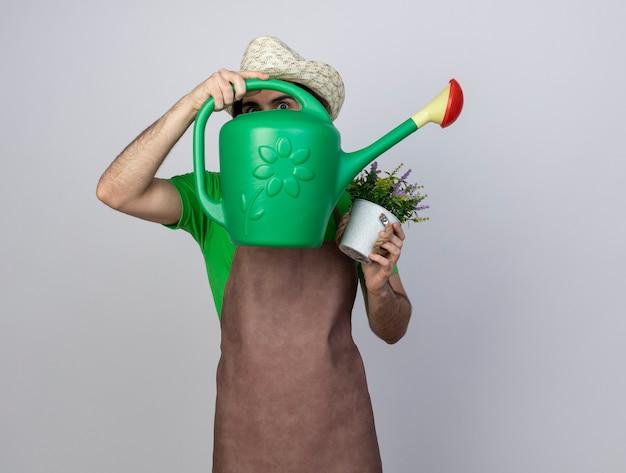 Zaskoczony młody ogrodnik mężczyzna w mundurze na sobie kapelusz ogrodniczy trzyma kwiat w doniczce i zakrył twarz konewką