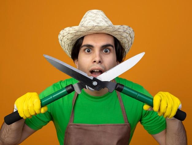 Zaskoczony młody ogrodnik mężczyzna w mundurze na sobie kapelusz ogrodniczy z rękawiczkami, trzymając maszynkę do strzyżenia na białym tle na pomarańczowej ścianie