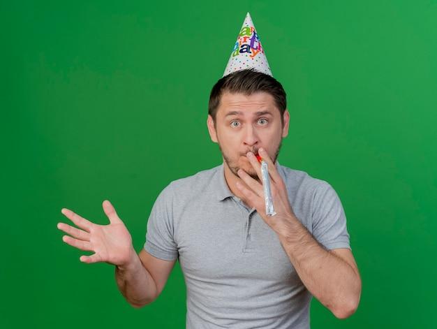 Zaskoczony, młody partyjny facet ubrany w czapkę urodzinową, trzymając i dmuchający gwizdek, rozkładając rękę na białym tle na zielono