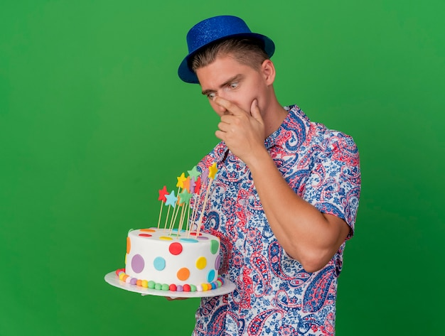 Zaskoczony, młody partyjny facet w niebieskim kapeluszu, trzymając i patrząc na ciasto, kładąc rękę na ustach na białym tle