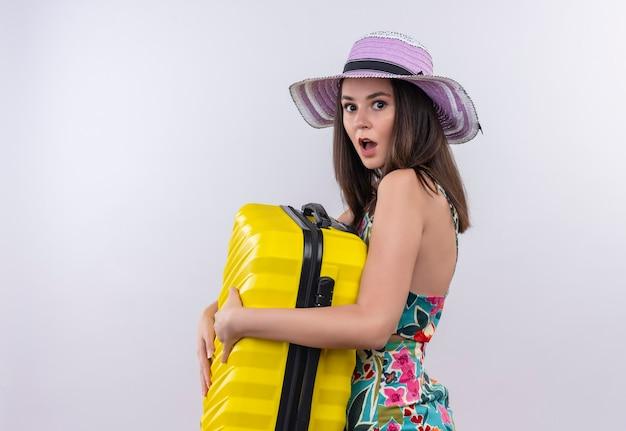 Zaskoczony młody podróżnik kobieta trzyma walizkę na odosobnionej białej ścianie