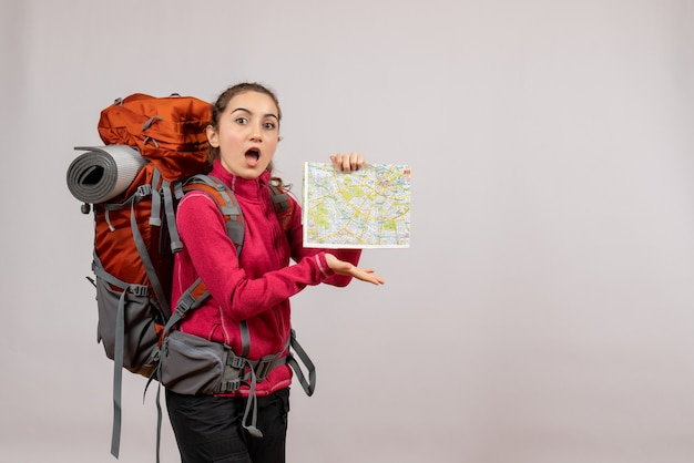 Zaskoczony młody podróżnik z dużym czerwonym plecakiem trzymającym mapę na szarym tle