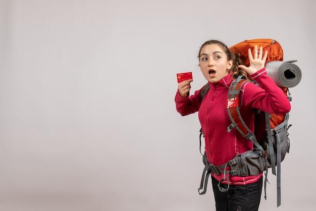Zaskoczony młody podróżnik z dużym plecakiem trzymającym machającą ręką kartą