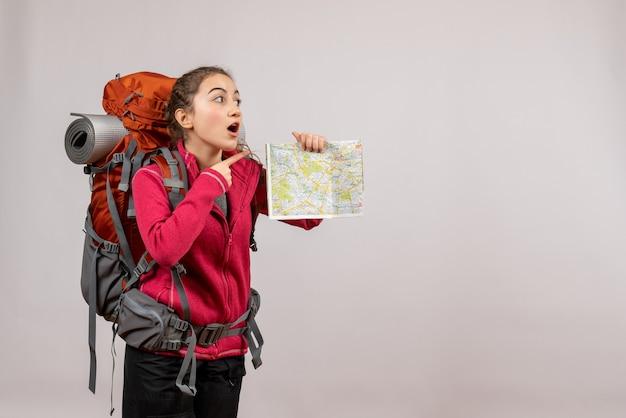 Zaskoczony młody podróżnik z dużym plecakiem trzymającym mapę na szarym tle