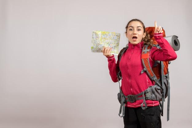Zaskoczony młody podróżnik z dużym plecakiem trzymającym mapę wskazującą palcem w górę