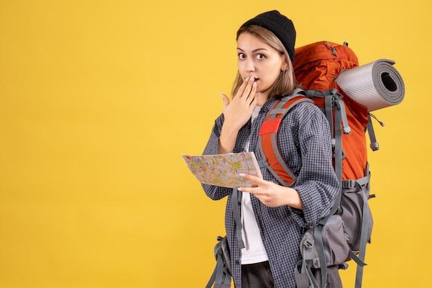 Zaskoczony młody podróżnik z plecakiem trzymającym mapę