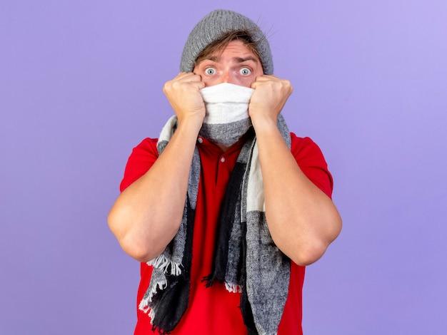 Zaskoczony, młody przystojny blondyn chory ubrany w czapkę zimową i szalik zakrywający usta szalikiem, patrząc na białym tle na fioletowej ścianie z miejsca na kopię