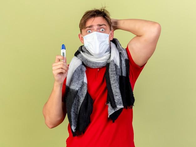 Zaskoczony, młody przystojny blondyn chory ubrany w maskę i szalik trzyma termometr, trzymając rękę za głową na białym tle na oliwkowej ścianie