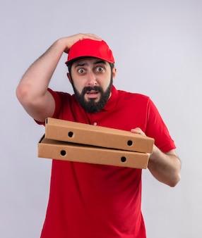 Zaskoczony młody przystojny doręczyciel ubrany w czerwony mundur i czapkę, trzymając pudełka po pizzy i kładąc rękę na głowie na białym tle na białej ścianie