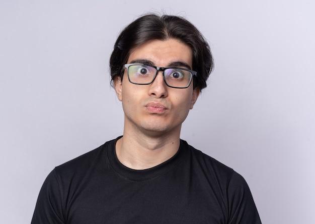 Zaskoczony, młody przystojny facet na sobie czarną koszulkę i okulary na białym tle na białej ścianie