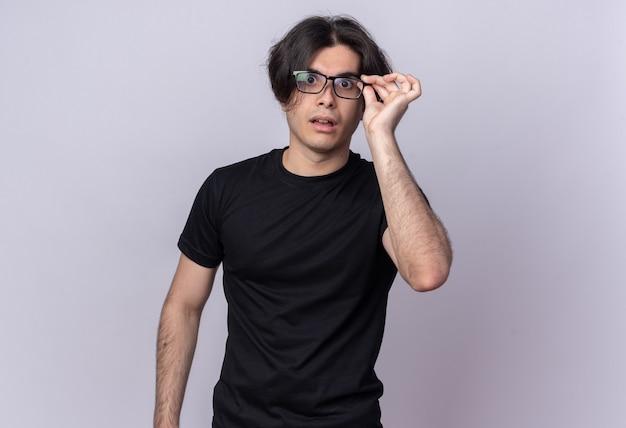 Zaskoczony, młody przystojny facet na sobie czarną koszulkę na sobie i trzymając okulary na białym tle na białej ścianie