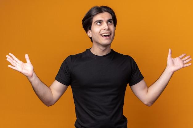 Zaskoczony, młody przystojny facet na sobie czarną koszulkę, rozkładając ręce na białym tle na pomarańczowej ścianie