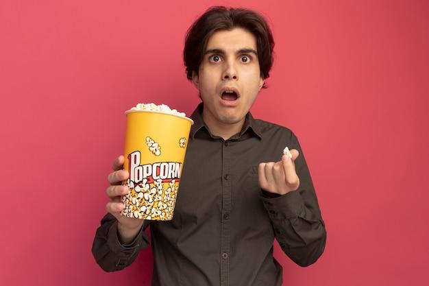 Zaskoczony, młody przystojny facet na sobie czarną koszulkę, trzymając wiadro popcornu i pokoju popcornu na białym tle na różowej ścianie