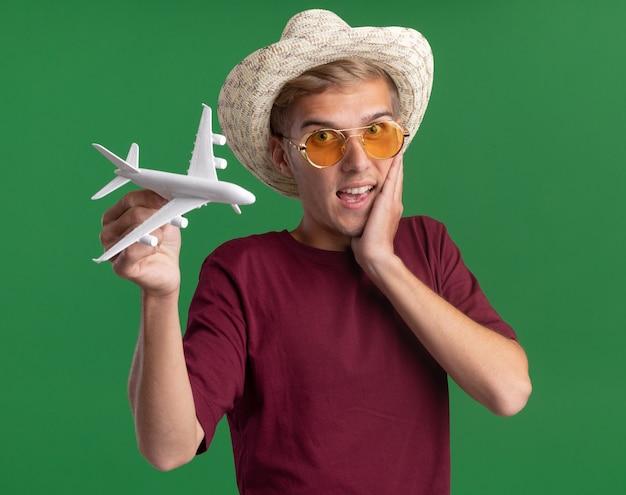 Zaskoczony, młody przystojny facet na sobie czerwoną koszulę z okularami i kapeluszem, trzymając samolocik kładąc rękę na policzku na białym tle na zielonej ścianie
