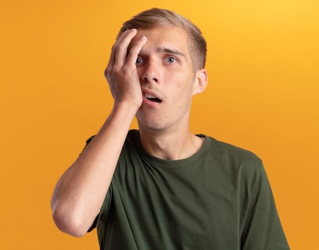 Zaskoczony, młody przystojny facet na sobie zieloną koszulę kładąc rękę na policzku na białym tle na żółtej ścianie