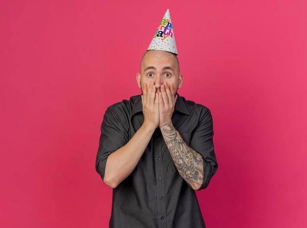Zaskoczony młody przystojny facet słowiańskich partii w kapeluszu urodzinowym, trzymając ręce na ustach, patrząc na przód na białym tle na różowej ścianie z miejsca na kopię