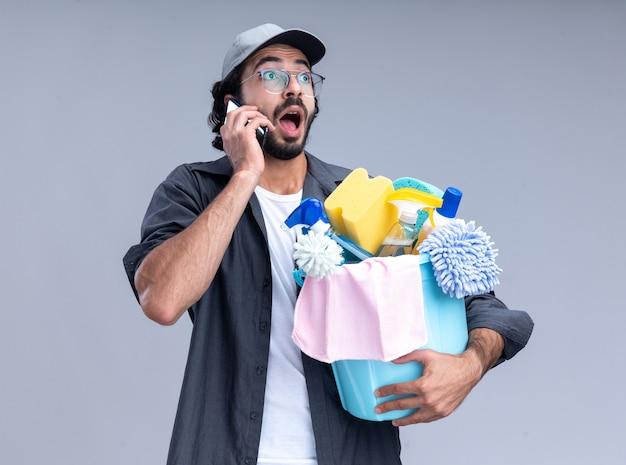 Zaskoczony, młody przystojny facet sprzątający sobie t-shirt i czapkę, trzymając wiadro narzędzi do czyszczenia i mówi przez telefon na białym tle na białej ścianie