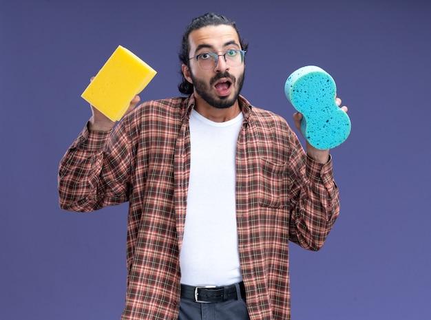 Zaskoczony, młody przystojny facet sprzątający sobie t-shirt, trzymając gąbki na białym tle na niebieskiej ścianie