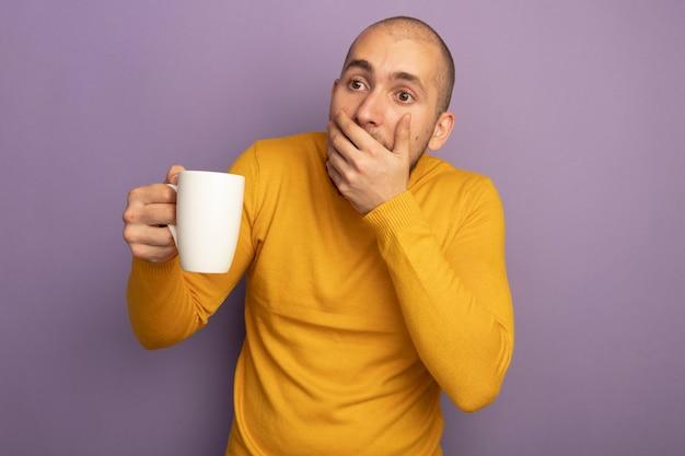 Zaskoczony, młody przystojny facet, trzymając i patrząc na filiżankę herbaty zakryte usta ręką odizolowaną na fioletowej ścianie