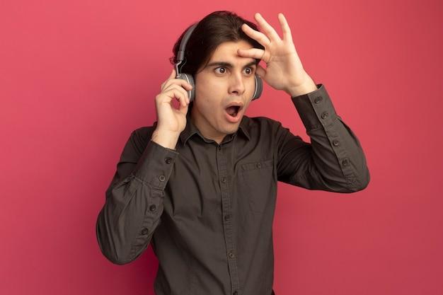 Zaskoczony młody przystojny facet ubrany w czarną koszulkę ze słuchawkami, patrzący na odległość ręką odizolowaną na różowej ścianie