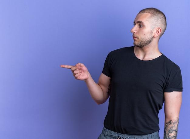 Zaskoczony młody przystojny facet ubrany w czarny t-shirt wskazuje z boku na białym tle na niebieskim tle z miejscem na kopię