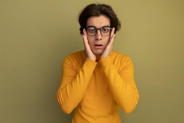 Zaskoczony młody przystojny facet ubrany w żółty sweter z golfem i okulary i kładąc ręce na policzkach na białym tle na oliwkowej ścianie