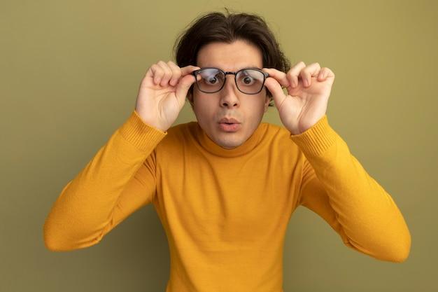 Zaskoczony, młody przystojny facet ubrany w żółty sweter z golfem, noszenie i trzymając okulary na białym tle na oliwkowej ścianie