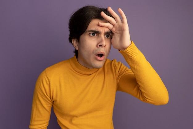 Zaskoczony, młody przystojny facet ubrany w żółty sweter z golfem, patrząc na odległość ręką odizolowaną na fioletowej ścianie