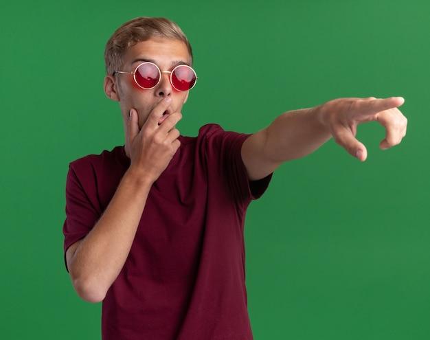 Zaskoczony, młody przystojny facet w czerwonej koszuli i okularach zakrył usta ręką i wskazuje na bok na białym tle na zielonej ścianie