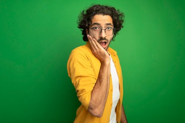 Zaskoczony, młody przystojny kaukaski mężczyzna w okularach, kładąc rękę na twarzy na białym tle na zielonej ścianie z miejsca na kopię