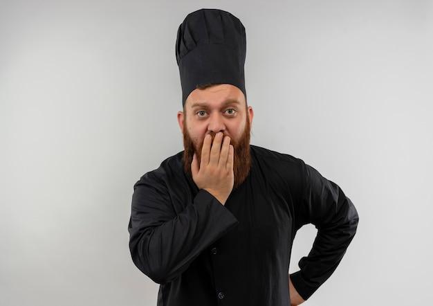 Zaskoczony, młody przystojny kucharz w mundurze szefa kuchni, kładąc dłoń na ustach ręką na talii na białym tle na białej przestrzeni