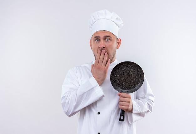 Zaskoczony, młody przystojny kucharz w mundurze szefa kuchni trzymając patelnię, kładąc rękę na ustach na białym tle