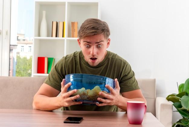 Zaskoczony, młody przystojny mężczyzna blondynka siedzi przy stole z kubkiem i telefonem, trzymając i patrząc na miskę frytek