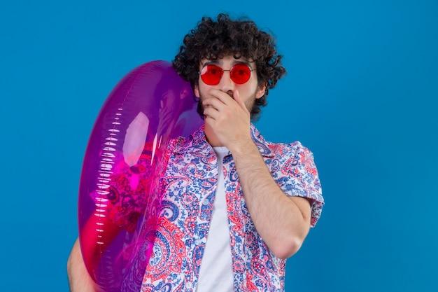 Zaskoczony, młody przystojny mężczyzna kręcone w okularach przeciwsłonecznych, trzymając pierścień do pływania z ręką na ustach na odosobnionej niebieskiej ścianie z miejsca na kopię