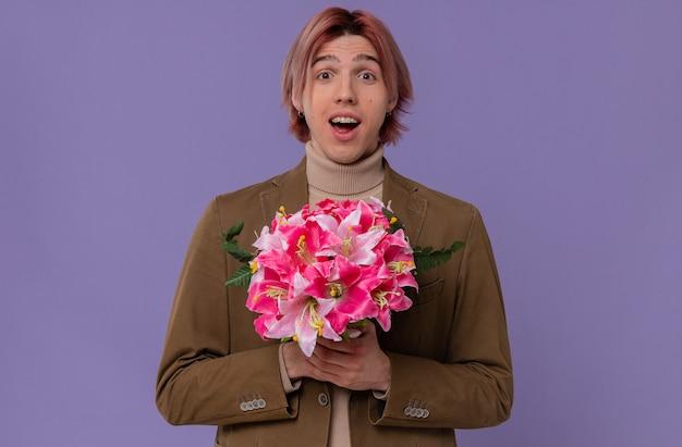 Zaskoczony młody przystojny mężczyzna trzyma bukiet kwiatów