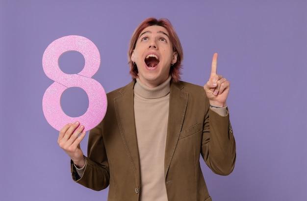 Zaskoczony młody przystojny mężczyzna trzyma różowy numer osiem, patrząc i wskazując w górę