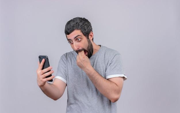 Zaskoczony, młody przystojny mężczyzna, trzymając i patrząc na telefon komórkowy i wkładając palce w usta na białym tle na białej ścianie
