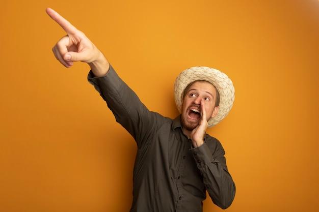 Zaskoczony młody przystojny mężczyzna w szarej koszuli i letnim kapeluszu krzyczy lub woła kogoś z ręką w pobliżu ust i wskazuje na coś palcem wskazującym